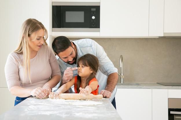 幸せなママとパパが一緒に焼きながら女の子に顔を染める。 無料写真