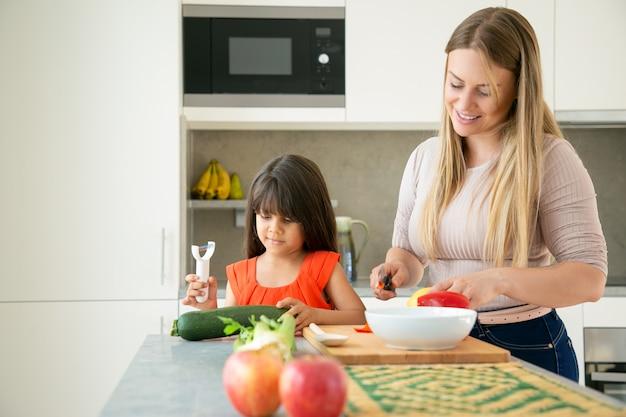幸せなママと娘が一緒に夕食を作ってくれます。少女と彼女の母親は、キッチンカウンターでサラダの野菜を剥離し、切断します。家族の料理のコンセプト 無料写真