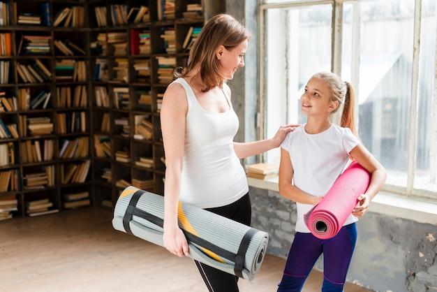 Счастливая мама и девушка держит коврики для йоги Бесплатные Фотографии