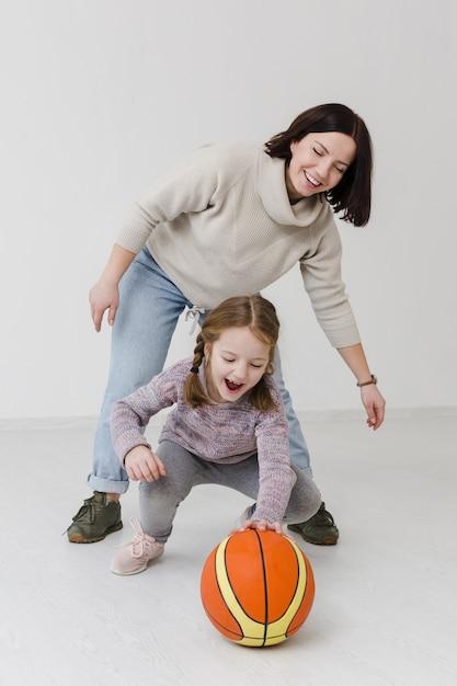 Счастливая мама и девушка играют в баскетбол Бесплатные Фотографии