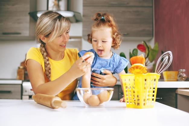 幸せなママと彼女の小さな娘が台所で料理 Premium写真