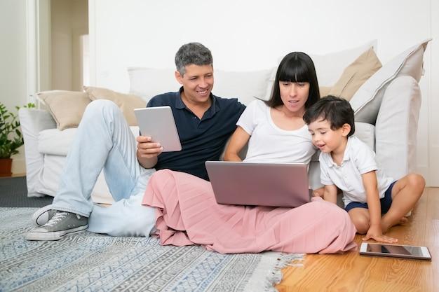 Счастливая мама, папа и милый маленький мальчик с помощью компьютеров, сидя на полу квартиры, наслаждаясь свободным временем вместе. Бесплатные Фотографии