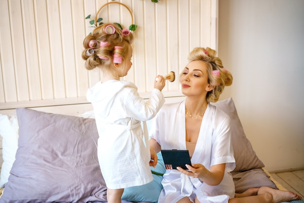 Happy mom and daughter make a make-up sitting on the bed in the bedroom Premium Photo