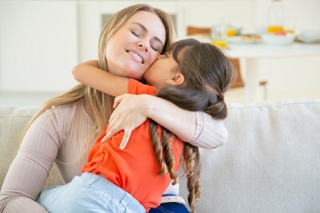 ソファの上の彼女の小さな女の子と一緒に座って、腕の中で子供を保持し、彼女を抱き締めて幸せなお母さん。 無料写真