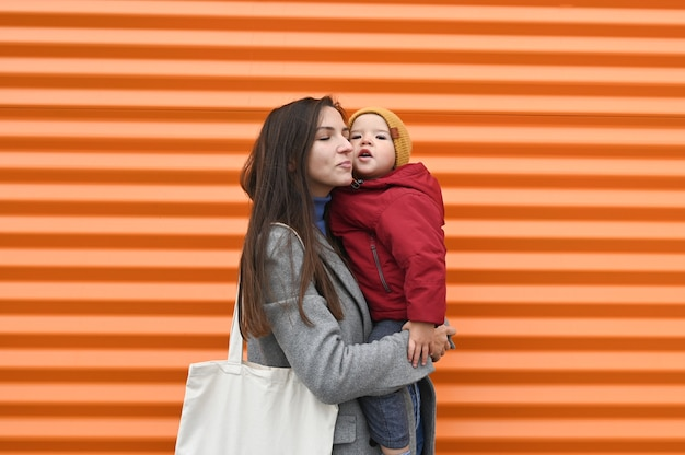 Счастливая мама с ребенком на апельсине Premium Фотографии