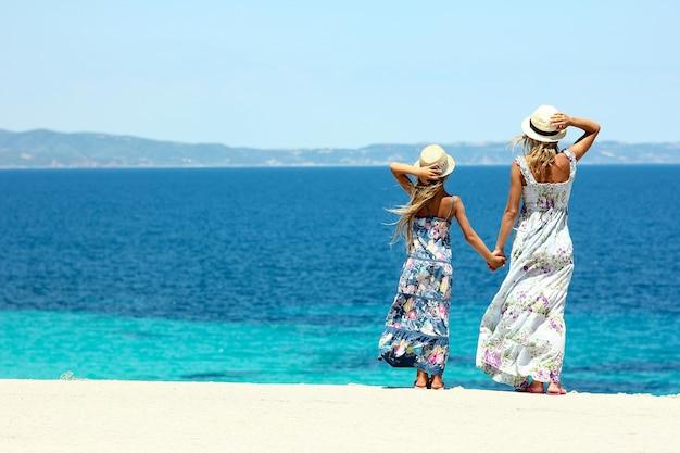 Счастливая мама с дочерью на берегу моря в шляпах и длинном платье Premium Фотографии