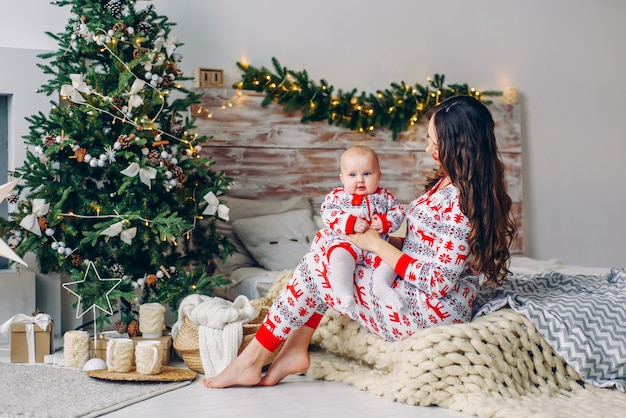 Happy mom with her little daughter in holiday clothing with printed deers and snowflakes having fun on the bed in cozy room with a christmas tree and christmas lights. new year and christmas concept. Premium Photo