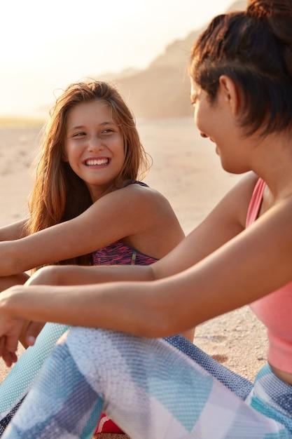 人生の幸せな瞬間。陽気な若いガールフレンドはレクリエーション時間を楽しんで、親友を前向きに見ています 無料写真