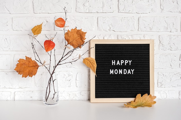Happy monday text on black letter board and bouquet of branches with yellow leaves on clothespins in vase on table Premium Photo