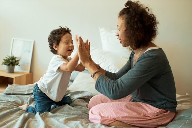 家でゲームをしている幸せな母と男の子。ベッドに座っている彼女の幼児の息子と手を握り締める陽気なラテン女性 無料写真