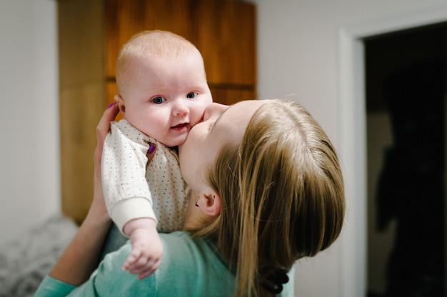 Счастливая мать и дочь. мама держит на руках и целует маленькую девочку, концепция счастливой семьи, образ жизни. новорожденный. фотосессия 4-5 месяцев. Premium Фотографии