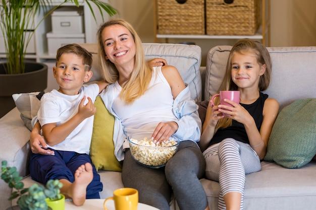Счастливая мать и ее дети едят попкорн Бесплатные Фотографии