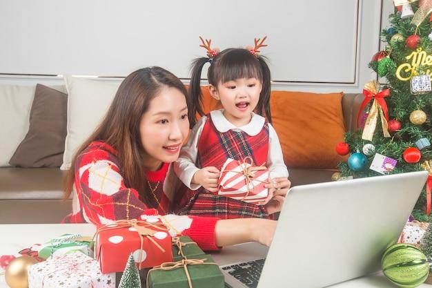 행복 한 엄마와 집에서 크리스마스 트리와 선물을 장식하는 작은 딸 무료 사진