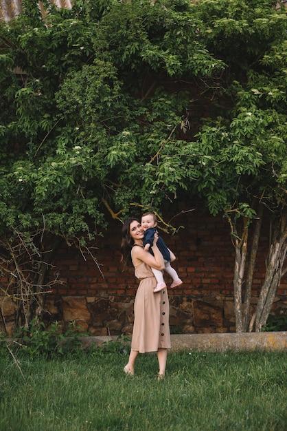 Счастливая мать и маленькая дочь, играя вместе в парке Premium Фотографии