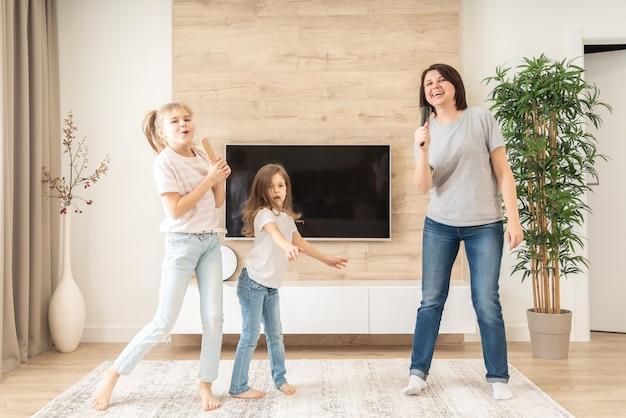 Счастливая мать и две дочери с удовольствием поют караоке в расческах. мать смеется, наслаждаясь смешные образ жизни деятельности с девочкой у себя дома вместе. Premium Фотографии