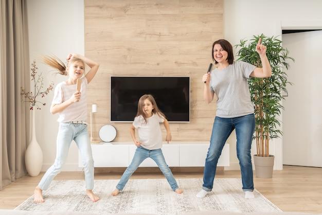 Счастливая мать и две дочери весело поют караоке в расчески. мать смеется, наслаждаясь забавным образом жизни с девочкой-подростком дома вместе. Premium Фотографии