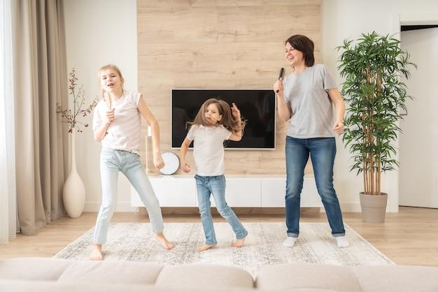 Счастливая мать и две дочери весело поют караоке в расчески. Premium Фотографии