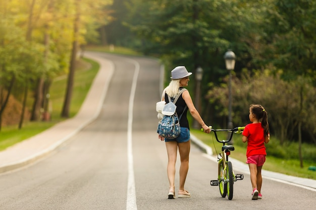 Happy mother and baby girl having fun in park with bicycle Premium Photo