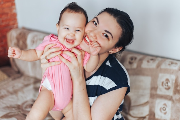 Happy mother and baby girl in pink clothes playing at home Premium Photo