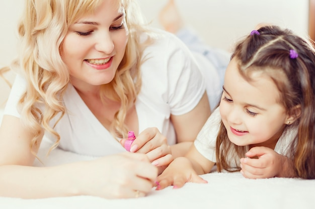 Happy mother and child daughter in hair curlers paint nails Premium Photo