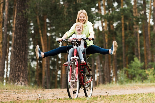 Happy mother and daughter on bicycle Free Photo