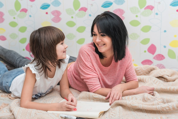 Happy mother and daughter drawing lying on bed Free Photo