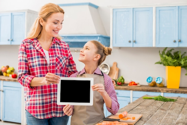 Happy mother and daughter holding digital tablet in hand looking at each other Free Photo
