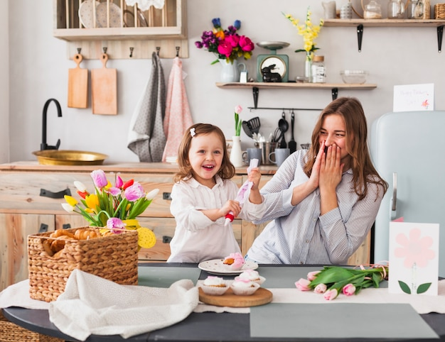 Happy mother and daughter making cupcake Free Photo