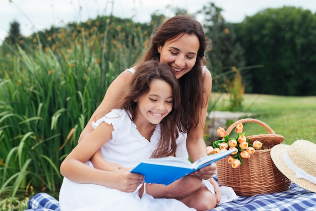 Happy mother and daughter reading book at picnic Free Photo