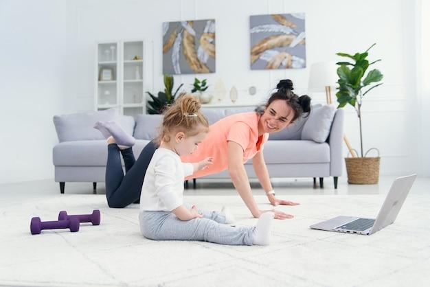 Счастливая мать делая тренировки утра в представлении йоги пока ее маленькая дочь играя дома. молодая прелестная мама имея потеху практикуя медитацию ослабляя на выходных без стресса с ребёнком. Premium Фотографии