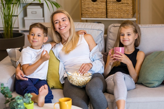Happy mother and her children eating popcorn Free Photo
