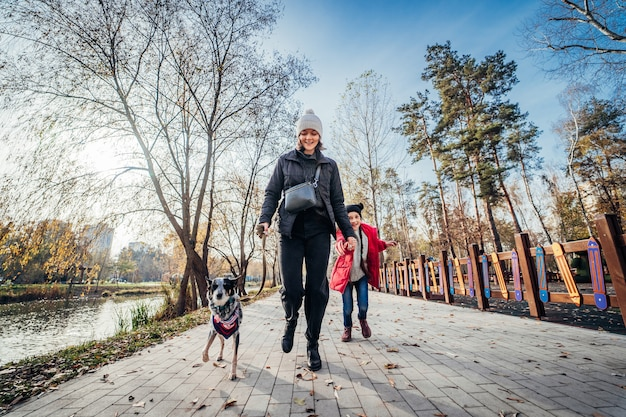 Happy mother and her daughter walk with dog in autumn park Free Photo