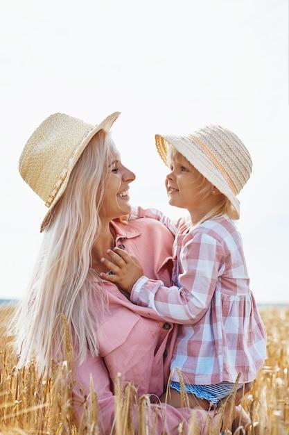 Счастливая мать, держащая ребенка, улыбаясь на пшеничном поле в солнечном свете. Premium Фотографии