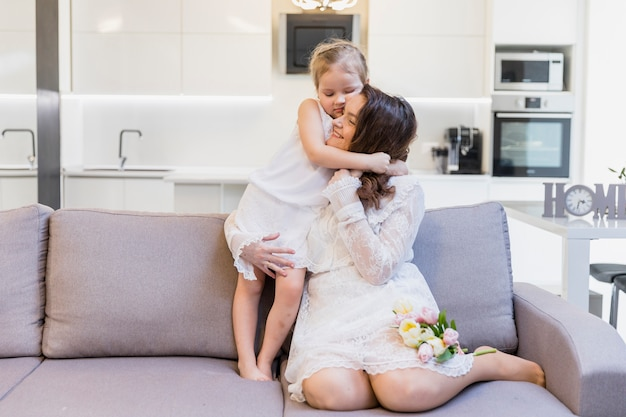 Happy mother hugging her cute little girl on sofa in living room Free Photo