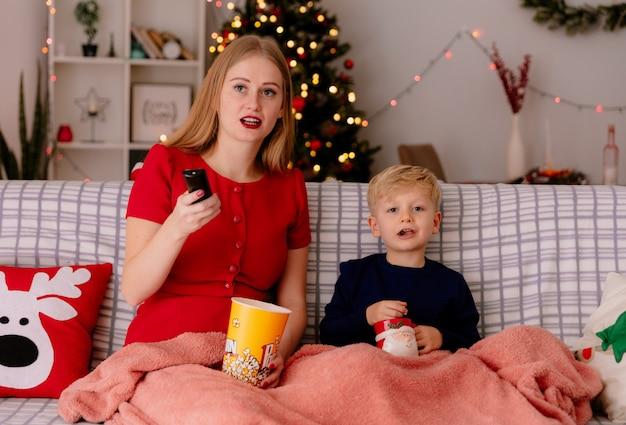 Счастливая мать в красном платье со своим маленьким ребенком сидит на диване под одеялом с ведром попкорна и вместе смотрит телевизор в украшенной комнате с рождественской елкой на заднем плане Бесплатные Фотографии