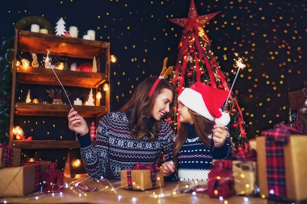 Happy mother and little girl in santa helper hat with sparklers in hands Premium Photo
