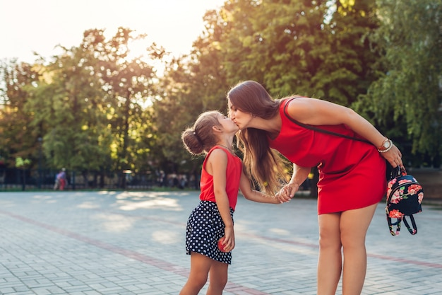 Happy mother meeting her daughters after classes outdoors primary school. family kissing. back to school Premium Photo