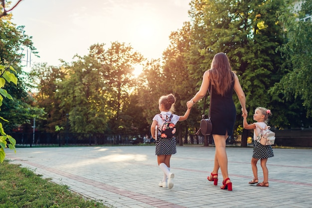 Happy mother meeting her kids daughters after classes outdoors primary school. Premium Photo