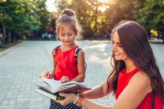 Happy mother met her daughter after classes outdoors primary school. Premium Photo