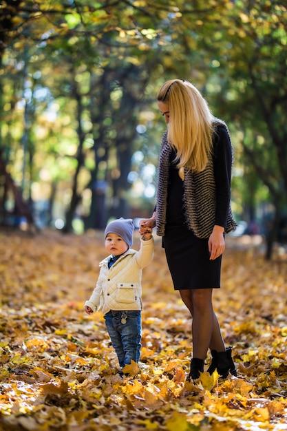 Счастливая мать, играя с ребенком в парке осенью. ребенок улыбается маме на руках Бесплатные Фотографии