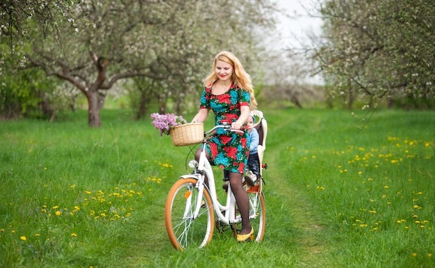 Happy mother riding city bicycle with baby in bicycle chair, in the basket lay a bouquet of lilacs Premium Photo