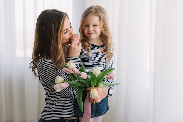 Happy mother's day. child daughter congratulates moms and gives her flowers tulips. Premium Photo