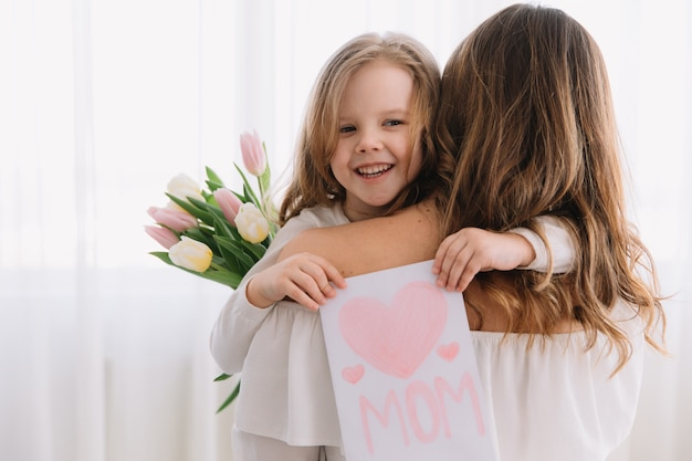 Happy mother's day. child daughter congratulates moms and gives her a postcard and flowers tulips. Premium Photo