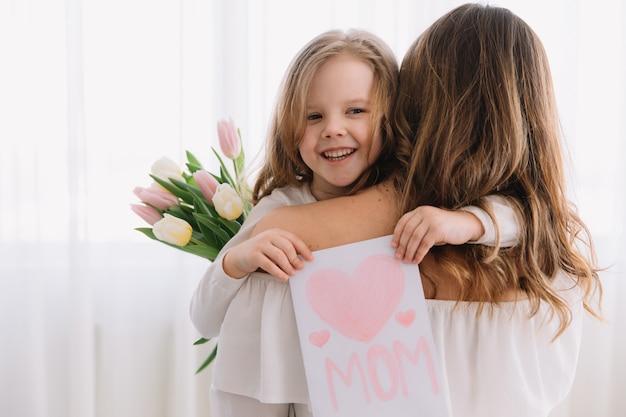 child daughter congratulates moms and gives her a postcard and flowers tulips Ini yang Dilakukan Agar Anak Makara Cerdas dan Keluarga Bahagia