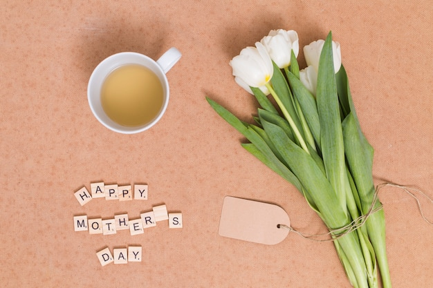 Happy mother's day text; lemon tea with white tulip flowers on brown backdrop Free Photo