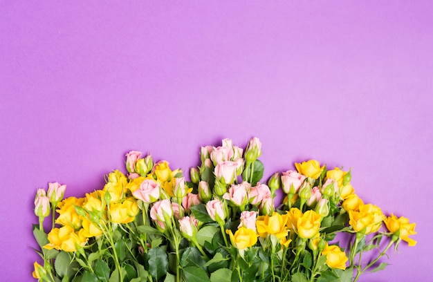 Happy mother's day with yellow pink roses flowers on purple table background Premium Photo