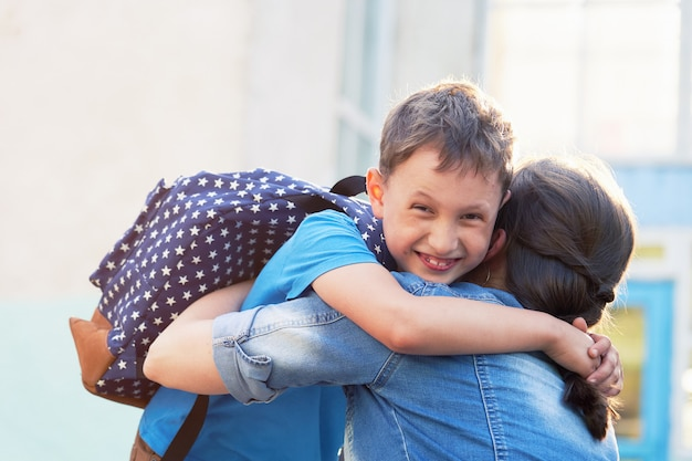 Happy mother and son embrace in front of the elementary school. Premium Photo