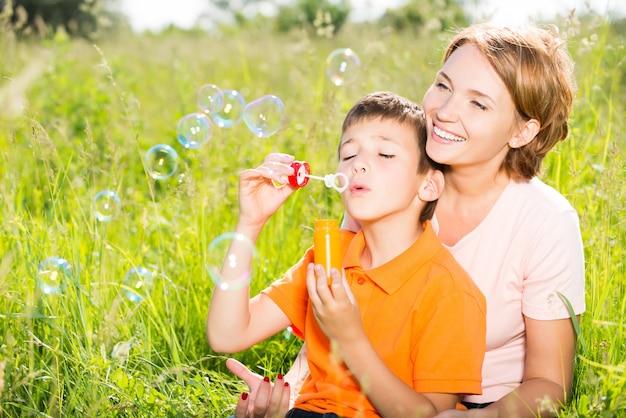 Felice madre e figlio nel parco che soffia bolle di sapone ritratto all'aperto Foto Gratuite