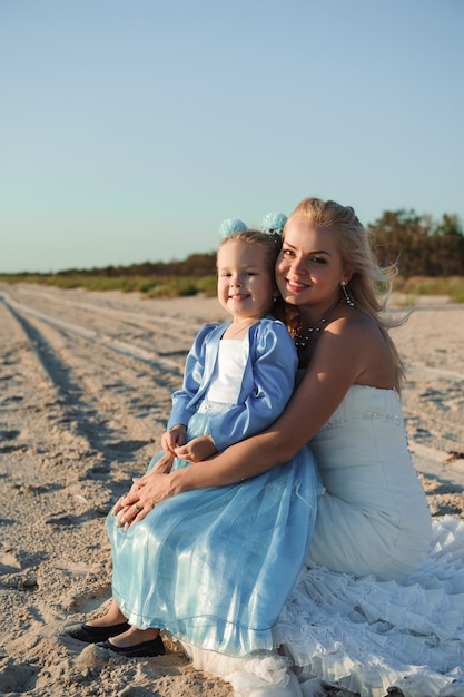 Happy mother in the wedding dress with her daughter on the beach Premium Photo