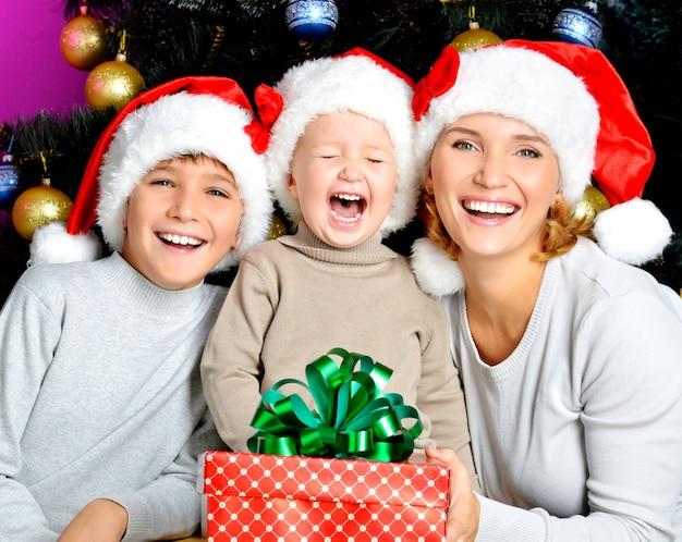 子供を持つ幸せな母親は、クリスマス休暇に新年の贈り物を保持します-屋内 無料写真